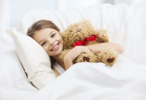 Girl sleeping with bear on Up And Under Linen and Mattress Protector